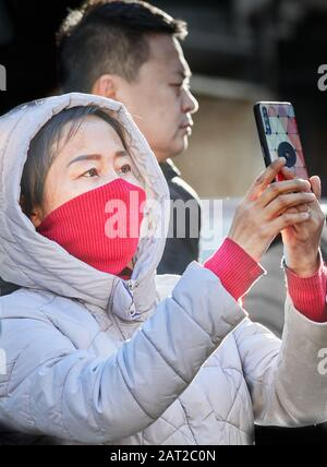 Face mask worn by a chinese tourist outside Trinity college, Cambridge, England, on 30 january 2020, to prevent catching the coronavirus flu. - Stock Photo