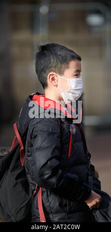 Face mask worn by a young chinese boy in Cambridge, England, on 30 january 2020, to prevent catching the coronavirus flu. - Stock Photo