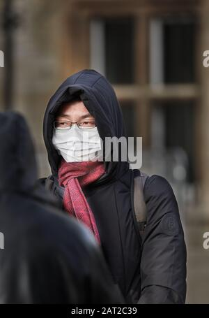 Face mask worn by a chinese tourist outside Gonville & Caius college, Cambridge, England, on 30 january 2020, to prevent catching the coronavirus flu. - Stock Photo