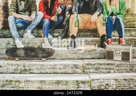 Group of friends drinking beer and eating takeout pizza outdoor -Young people sitting in staircase having fun listening music - Friendship, party, soc