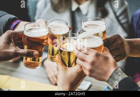 Group of friends enjoying a beer in brewery pub - Young people hands cheering at bar restaurant - Friendship and youth concept - Warm vintage filter -