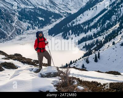 A tourist in the mountains stands against the backdrop of a frozen mountain lake. Trekking in the winter mountains - Stock Photo