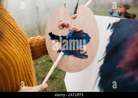 Close up photo of young female artist working on painting outdoors. She holds oil paints, artist brushes, canvas and palette. She is mixing colours on - Stock Photo