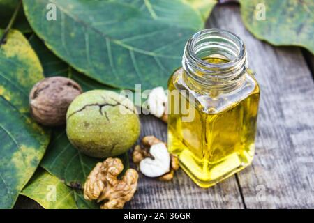 Walnut oil in a glass jar near walnuts and green leaves on a wooden table. Healthy food. - Stock Photo