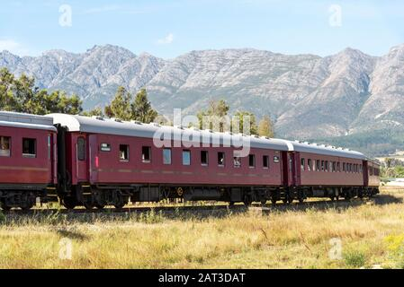 Wolseley, Swartland region, South Africa. Dec 2019. Steam train excursion passing through the Swartland region with a mountain backdrop. - Stock Photo