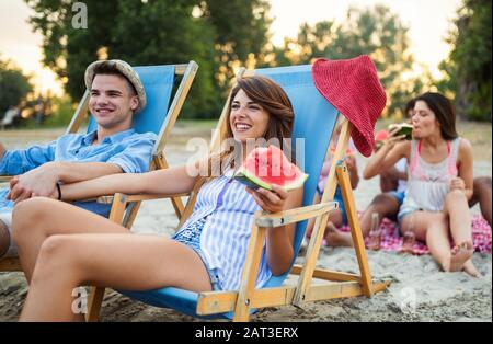 Happy friends having fun on the beach and eating watermelon. - Stock Photo