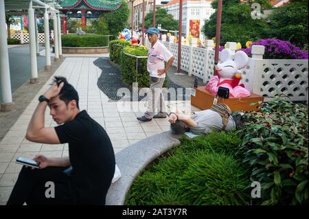 23.01.2020, Singapore, Republic of Singapore, Asia - Three men in a public park located above New Bridge Road and Eu Tong Sen Street in Chinatown.