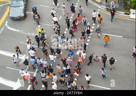 23.01.2020, Singapore, Republic of Singapore, Asia - Pedestrians cross a street in the Chinatown district.