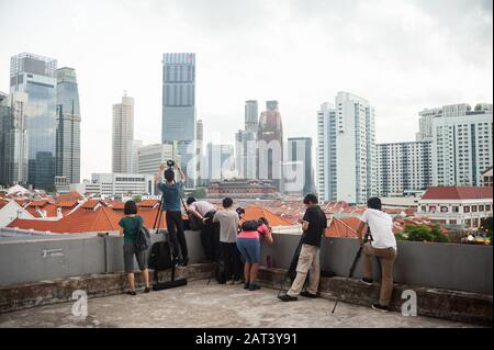 23.01.2020, Singapore, Republic of Singapore, Asia - People stand on a roof and photograph the cityscape of Chinatown and the city skyline.