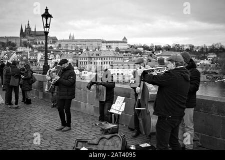 Prague, Czech Republic - 01 January 2020: street musicians are playing music on the Charles Bridge near a lamppost - Stock Photo
