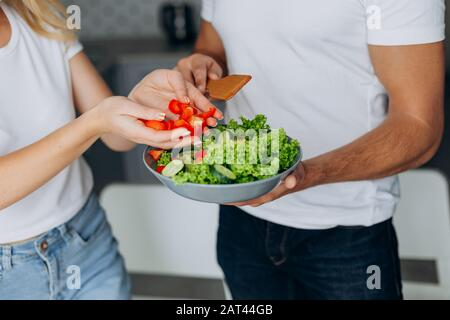 Closeup male and female hands cooking healthy food .  Man holding salad plate Stock Photo