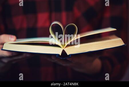 Close up of reader hands holding an open book with the heart symbol shape made of pages. Love education concept as student boy reads a textbook isolat - Stock Photo