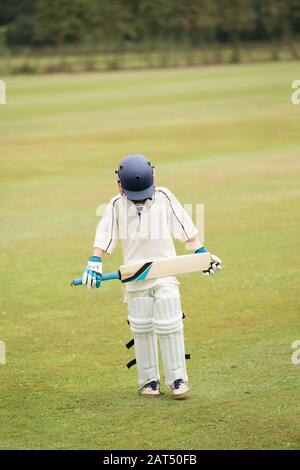 Cricket, a young cricketer with head bowed after defeat, isolated against a green grass background. - Stock Photo