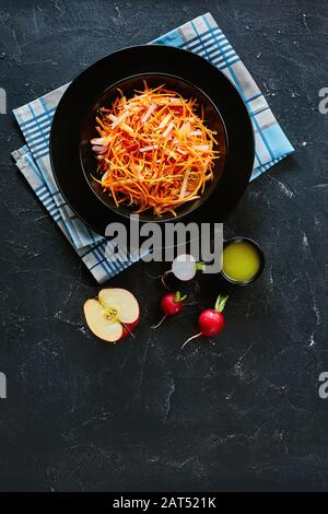 Fresh carrot radish and apple salad sprinkled with quinoa seeds and lemon zest in a black bowl on a wooden table with ingredients, vertical view