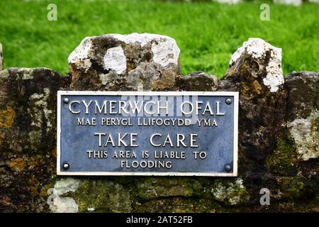 Sign in Welsh and English warning of flooding risk on wall of car park for Ogmore Castle, South Glamorgan, Wales, UK - Stock Photo
