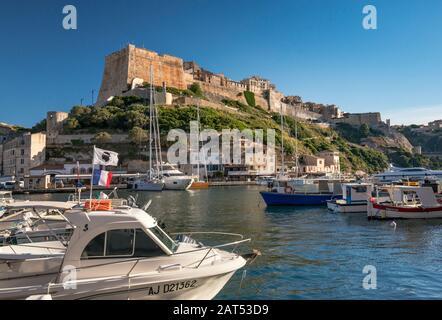 Citadelle, boats at marina at port at sunset, in Bonifacio, Corsica, France - Stock Photo