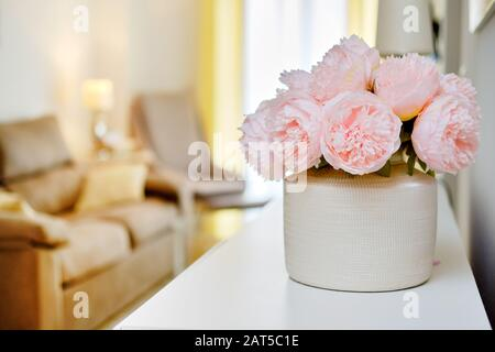 Pretty pink colour peonies flowers in white vase inside of light warm living room, selective close up focus on bouquet, no people