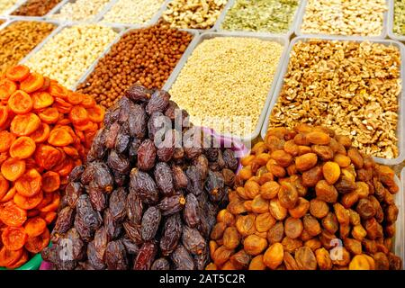 Dates, dried apricots are sold in the market on the background of various nuts, almonds, hazelnuts, walnuts, cashews in motion blur. - Stock Photo