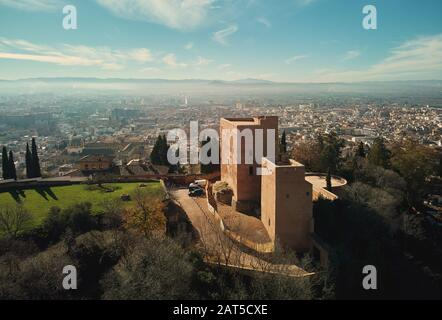 Aerial picturesque drone point of view Granada castle surrounding lands and cityscape, Alhambra or Red Castle, located on top of hill al-Sabika. Spain