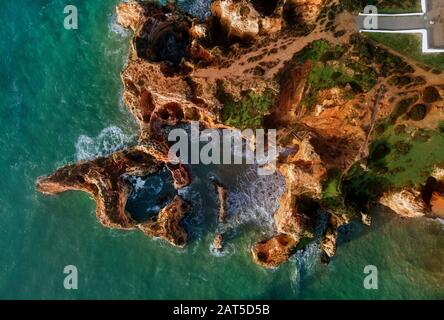 Aerial photo view Ponta da Piedade headland with group of rock formations yellow-golden cliffs along limestone coastline, Lagos, Portugal - Stock Photo