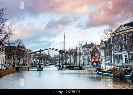 The center of Schiedam with beautiful narrow streets and small canals, photo taken in the evening hours with beautiful orange and blue clouds. Provinc - Stock Photo
