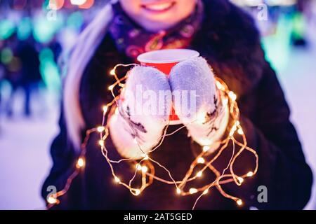 Girl holds cardboard glass with coffee or hot tea in winter in warm mittens