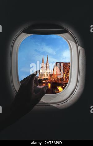 Airplane window with a aerial panorama of Cologne, Germany and Cologne Cathedral with a bridge in the evening during a flight