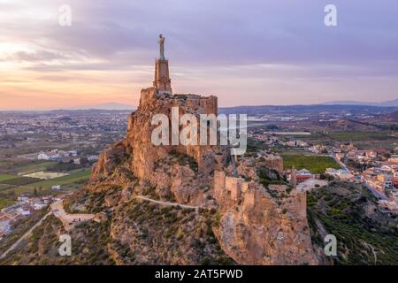 Monteagudo medieval castle ruin twelve rectangular towers circling the hilltop and the sacred heart of Jesus Christ statue on top near Murcia Spain