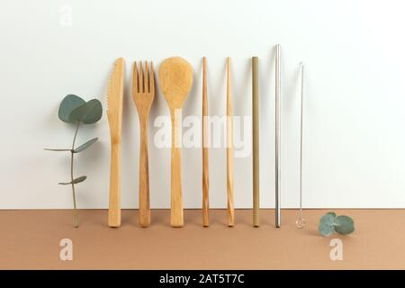 Eco friendly bamboo cutlery set and eucalyptus leaves on a white background. Zero waste concept. - Stock Photo