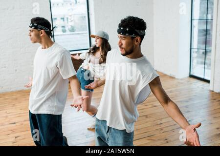 selective focus of multicultural men in headbands and young woman in cap dancing hip-hop - Stock Photo