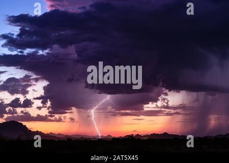 Lightning strikes from a thunderstorm at sunset in the desert near Tonopah, Arizona. - Stock Photo