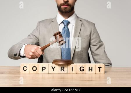 cropped view of judge holding gavel near wooden cubes with copyright inscription isolated on grey