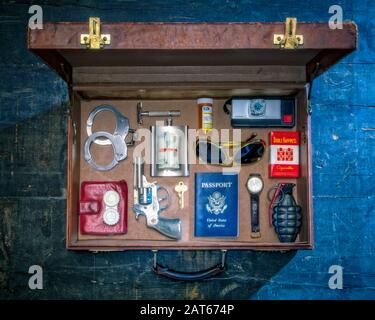 An overhead view of an old style leather briefcase with dangerous travel items carefully arranged inside in an orderly fashion - Stock Photo