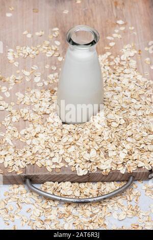 Vegan plant based milk alternatives. Oat Milk and oats on a wooden board - Stock Photo