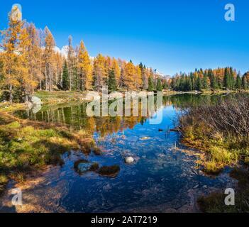 Autumn alpine mountain lake near San Pellegrino Pass, Trentino, Dolomites Alps, Italy. Picturesque traveling, seasonal and nature beauty concept scene - Stock Photo
