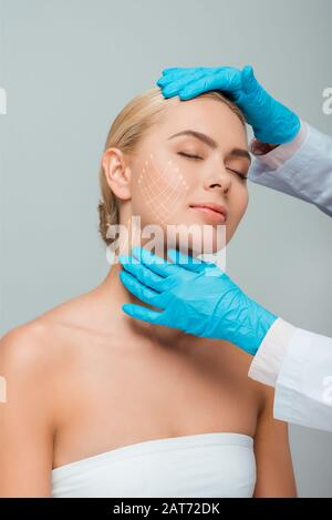 cropped view of beautician in blue latex gloves touching woman with closed eyes and plastic surgery marks on face isolated on grey - Stock Photo