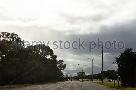 Gloomy overcast sky with sunlight breaking through clouds over asphalt city road with trees and lampposts on roadsides and buildings in distance in su - Stock Photo