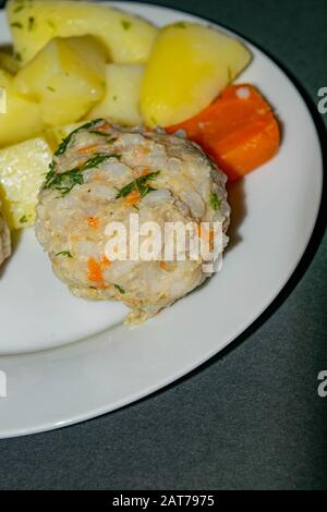 meat meatballs with boiled potatoes and boiled carrots on a white plate on a dark background. Close up - Stock Photo