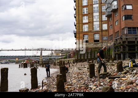 A man with metal detector works his way along the river Thames foreshore looking towards the shard building. With ancient posts exposed, is a popular place for mudlarking and archaeological finds. - Stock Photo