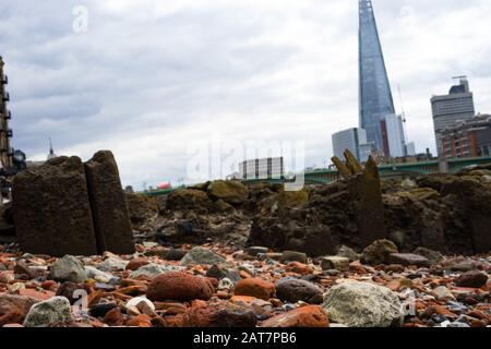 Pebbles on the foreshore of the River Thames looking towards  the shard building. A popular place for mudlarking and archaeological finds. - Stock Photo
