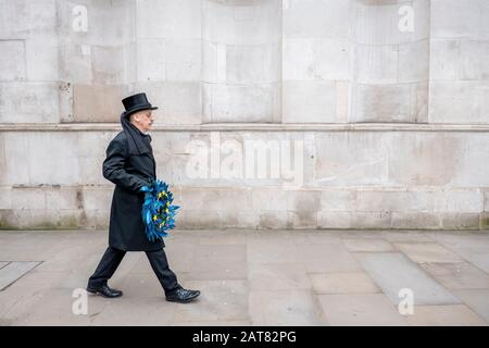 London, UK. 31 January 2020. A man dressed as an undertaking slowly walks along Whitehall holding a European Union funeral reef with 11 yellow stars. - Stock Photo