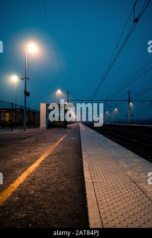 Empty European Railroad Station at Dusk with a One Point Perspective in France with Misty Conditions.Thick fog settles over railroad tracks at night. - Stock Photo