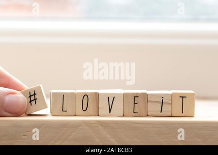 Wooden cubes with a hashtag and the words love it, social media concept background - Stock Photo