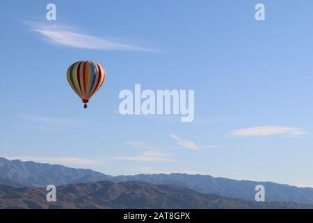 a hot air balloon sky over mountains and desert - Stock Photo