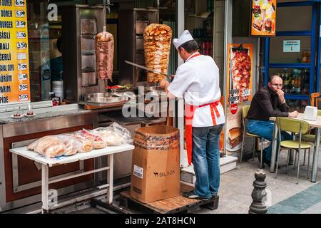 Istanbul, Turkey - June 8 2014: Cook Cutting Meat From a Doner Kebab for a Customer in a Turkish Street Food Restaurant.
