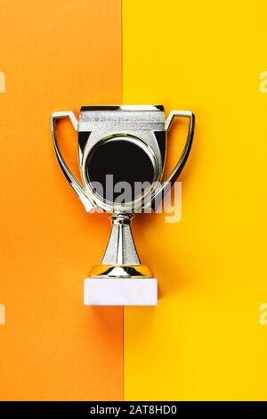 Golden winner cup as trophies on bright orange-yellow background Stock Photo