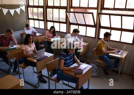 Teenagers in school classroom - Stock Photo