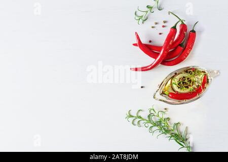 Oil with chili spice and herbs. Fresh chili peppers and rosemary top view on white background. Copy space. - Stock Photo