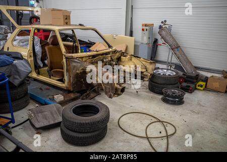 in a garage there is a disassembled old car wreck to be restored - Stock Photo