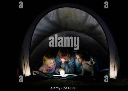 Girls laying in a camping tent wrapped in a sleeping bag with dog reading a book with flashlight at night during summer holidays - Stock Photo